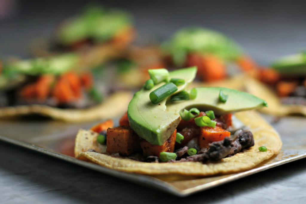 Roasted Sweet Potato Tostadas Chili scented roasted sweet potatoes, smashed black beans, salsa and avocado served up on a crisp corn tortilla! No utensils needed making these tostadas the ultimate finger food...perfect for a New Year's Eve Party!
